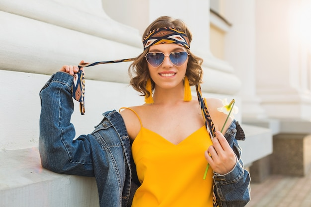 Beautiful sexy stylish woman in yellow stylish dress wearing denim jacket, trendy outfit, spring summer fashion trend, sunny, blue sunglasses, street fashion, hipster style, fashionable accessories