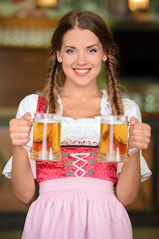 Beautiful, sexy waiter woman holding glasses of beer.