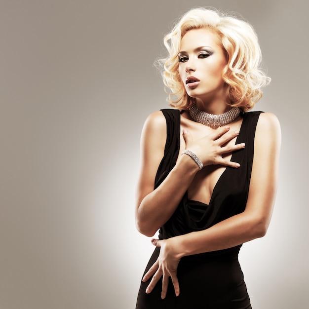 스튜디오에서 포즈를 취하는 검은 드레스에 아름 다운 섹시 한 백인 여자