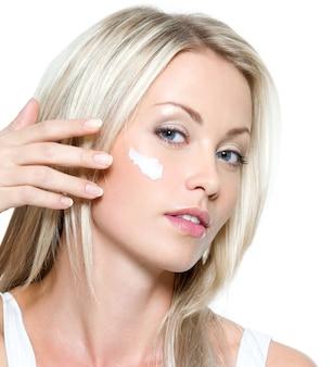 Красивая сексуальная женщина, наносящая косметический крем на лицо - изолированные