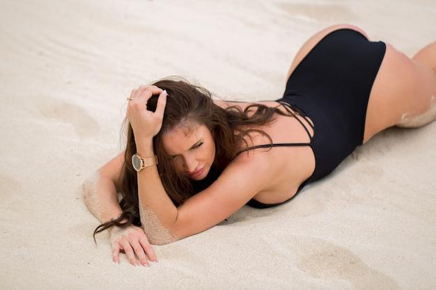 Beautiful sexy woman in black bikini lies on the white sand on the beach