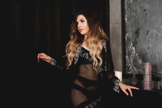Beautiful sexy woman in black peignoir near fireplace