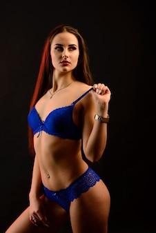 Beautiful sexy woman in blue underwear on a dark background, perfect female body, studio shot