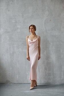 Красивая сексуальная женщина в светло-бежевом шелковом платье. шум, не в фокусе