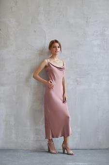 ライトベージュのシルクのドレスを着た美しいセクシーな女性。