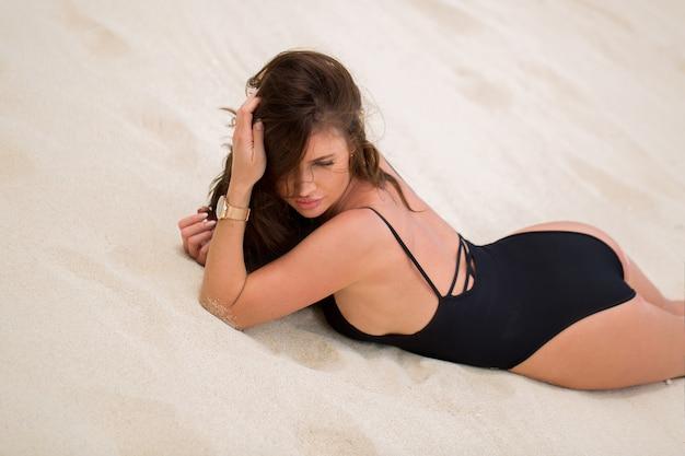 黒いビキニの美しいセクシーな女性は、ビーチの白い砂の上に横たわっています