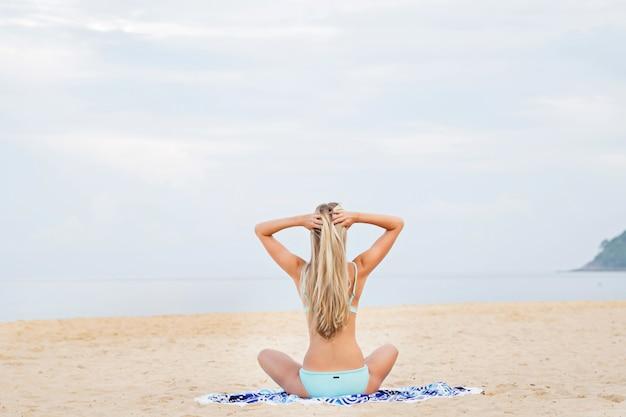 Красивая сексуальная женщина в голубом бикини на песчаном пляже