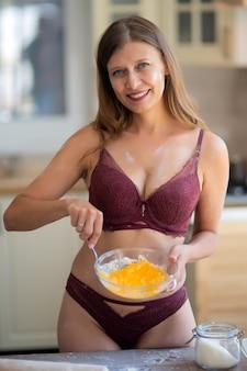 自宅のキッチンでランジェリーの美しいセクシーな女性
