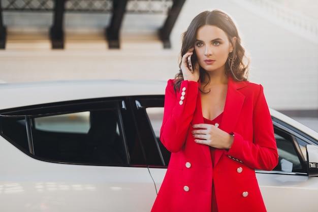 電話でビジネスで話している車でポーズをとって赤いスーツの美しいセクシーな女性