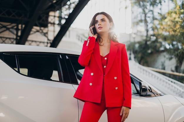 전화 사업에 얘기하는 차에서 포즈를 취하는 빨간 옷에 아름 다운 섹시 한 여자