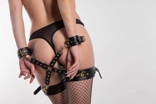 Красивая сексуальная женщина в чулках и бдсм-наряде со спиной