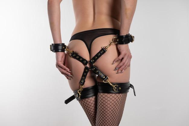 Красивая сексуальная женщина в чулках и бдсм-наряде со спиной Premium Фотографии