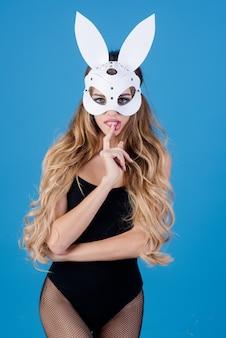 Красивая сексуальная женщина в маске белого кролика делает жест шшш и выглядит очень чувственно сексуальной девушкой-моделью