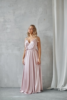 Beautiful sexy woman in a light beige silk dress