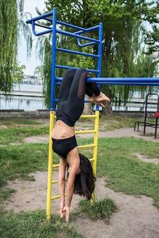 美しいセクシーな女性は完璧なストリートワークアウトのために鉄棒晴れた日に運動をします。健康的な生活様式