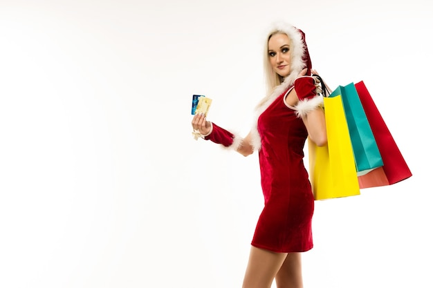 A beautiful sexy woman in a new year's dress, hold in hands credit cards and shopping bags isolated on white. celebration of christmas or new year sale