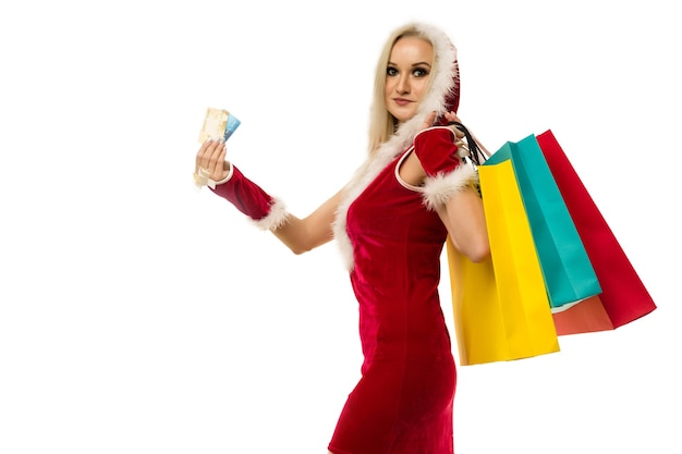 A beautiful sexy woman in a new year's dress, hold in hands credit cards and shopping bags