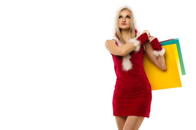 A beautiful sexy woman in a new year's dress, hold in hands shopping bags isolated on white. celebration of christmas or new year sale