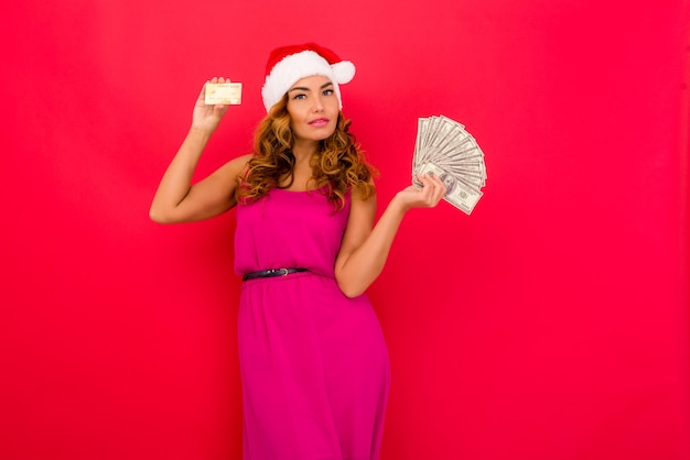 A beautiful sexy woman in a new years hat hold in hands money and credit card