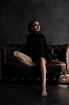暗い部屋の革のソファの上の美しいセクシーな女性