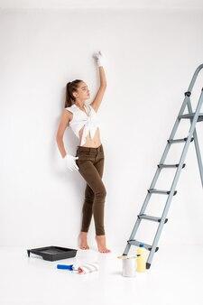 Красивая сексуальная женщина красит стену в своем доме