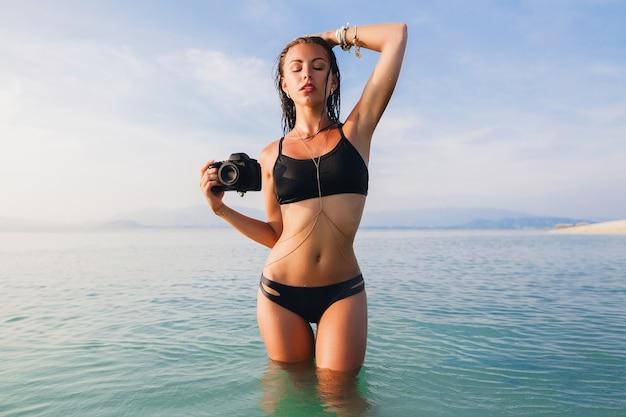Bella donna sexy, corpo snello perfetto, pelle abbronzata, costume da bagno bikini nero, in piedi in acqua blu, tenendo in mano una macchina fotografica digitale, calde vacanze estive tropicali, tendenza della moda, vita, pancia, fianchi