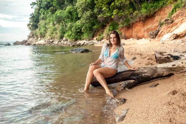 Beautiful sexy woman sitting on big branch on sea shore