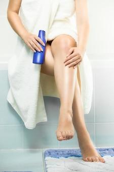 バスルームに座って、入浴後に脚にローションを塗る美しいセクシーな女性