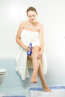 아름 다운 섹시 한 여자 화장실에 앉아 다리에 로션을 적용