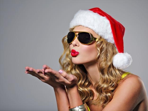 산타 모자에 웃는 아름 다운 섹시 한 여자. 예쁜 여자가 키스를 보냅니다. 매력적인 젊은 여자는 작은 크리스마스 트리를 보유-스튜디오에서 포즈