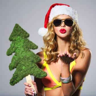サンタの帽子で笑っている美しいセクシーな女性。