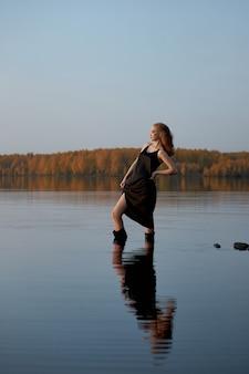 아름 다운 섹시 한 여자는 석양의 광선에 연못에 의해 물에 서