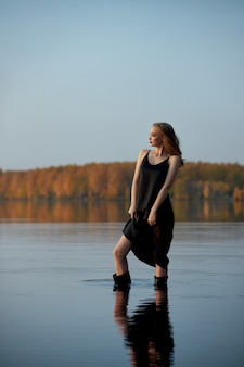 Beautiful sexy woman stands in the water by the pond in the rays of the setting sun