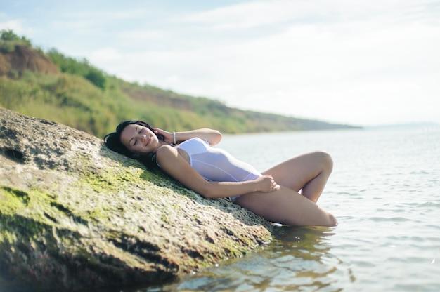 Красивая сексуальная женщина, загорая на пляже и отдыхая у моря.