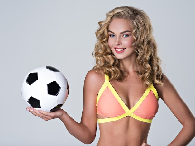 Beautiful sexy woman in trendy swimsuit holds a soccer ball.