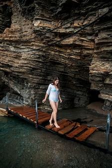 海の洞窟で木の小道を歩く美しいセクシーな女性