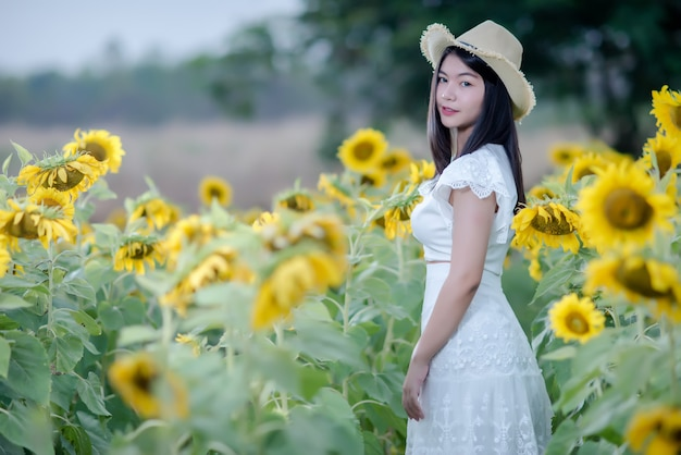 Beautiful sexy woman in a white dress walking on a field of sunflowers