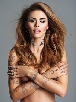 몸에 문신과 아름 다운 섹시 한 여자. 갈색 머리를 가진 젊은 성인 섹시 한 여자의 초상화. 누드 몸매와 가슴에 팔을 교차시킨 섹시한 여성.