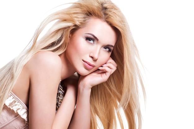 Bella donna sexy con capelli lunghi biondi e trucco professionale in posa - isolato su bianco.