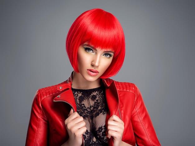Красивая сексуальная женщина с ярко-красной прической боб. манекенщица. чувственная шикарная девушка в кожаной куртке. сногсшибательное лицо симпатичной дамы.