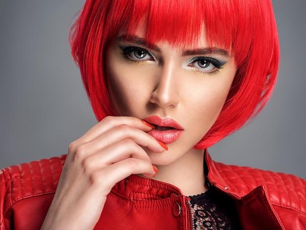 真っ赤なボブの髪型を持つ美しいセクシーな女性。ファッションモデル。革のジャケットで官能的なゴージャスな女の子。きれいな女性の見事な顔。
