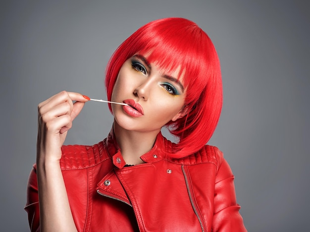 Beautiful sexy woman with bright red bob hairstyle. fashion  model. sensual  gorgeous girl in a leather jacket. stunning face of a pretty lady. bright girl stretches gum