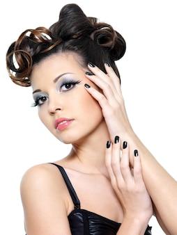 Bella donna sexy con acconciatura creativa e unghie nere. trucco occhi alla moda