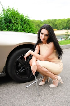 Beautiful sexy woman with dark hair on a background of a car with a wrench