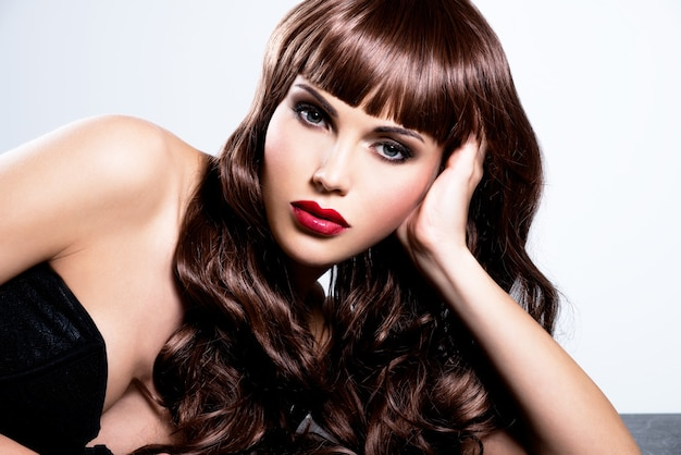 Bella donna sexy con lunghi capelli ricci. ritratto di un modello femminile con il trucco di moda.