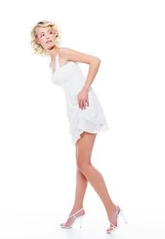 Красивая сексуальная женщина в современном белом платье позирует в студии, глядя в сторону