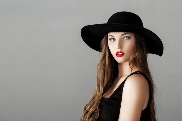 Красивая сексуальная женщина с красной помадой в черной шляпе