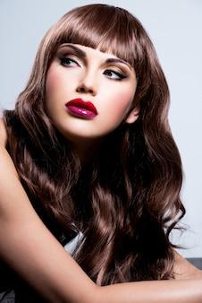 スタジオでポーズをとって赤い爪と唇を持つ美しいセクシーな女性。