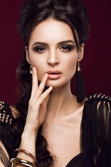 Beautiful sexy woman with sensual lips, fashion hair, black dress and gold accessories