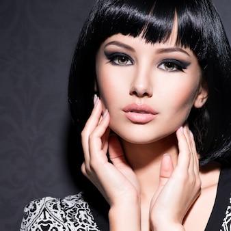 Красивая сексуальная женщина с короткими черными волосами позирует